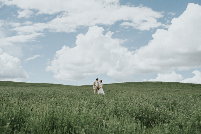 calgary wedding photographers. bride and groom standing in field.