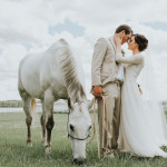 Bride and groom with white horse. Cowboy Wedding