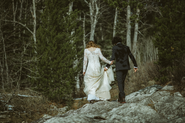 bride and groom walking in forrest