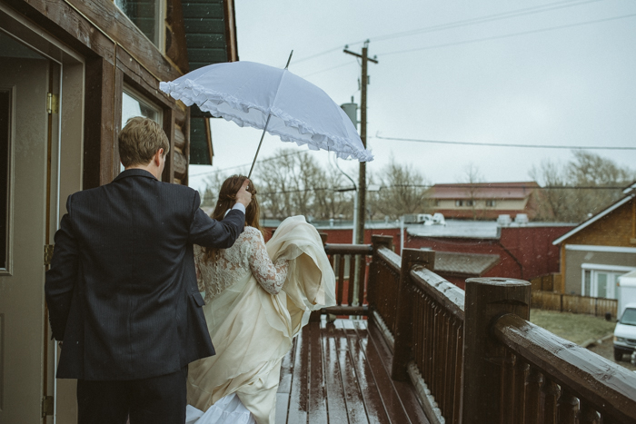 Bride standing under umbrella in the rain.