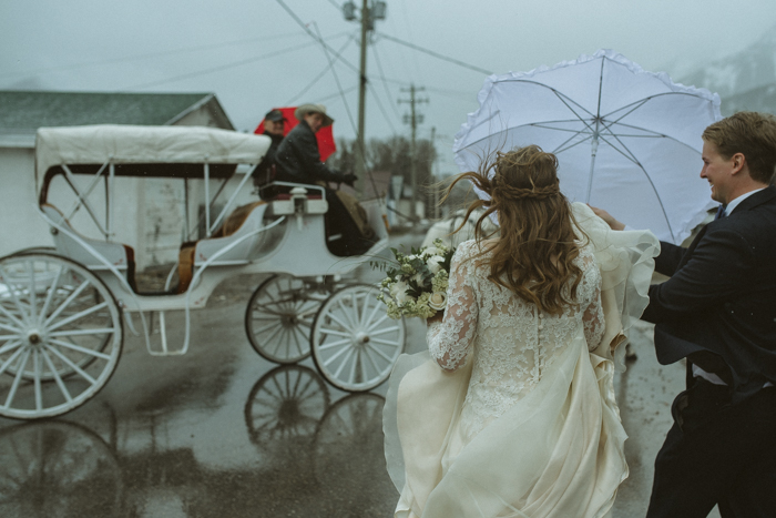 Bride getting into white carriage pulled by white horses while raining