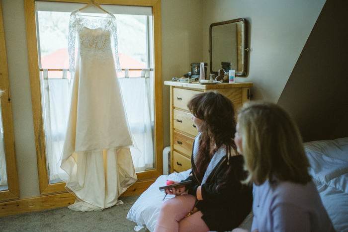 Bride getting ready at Cabin in Waterton. Dress hanging in Window.
