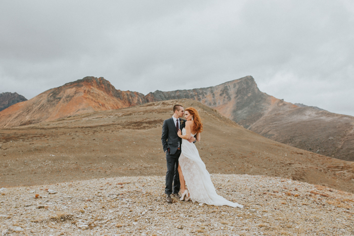Helicopter Elopement Wedding Banff. Bride and groom on top of mountain. Mountain top wedding.