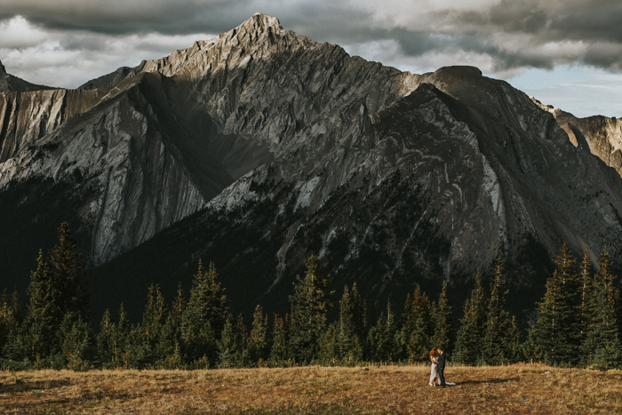 Helicopter Elopement Wedding Banff. Calgary Bride and Groom standing on top of mountain. Mountain top views for wedding pictures.
