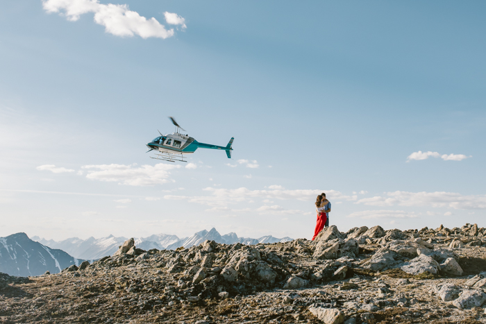 helicopter engagement session on top of mountain. helicopter flying in background.