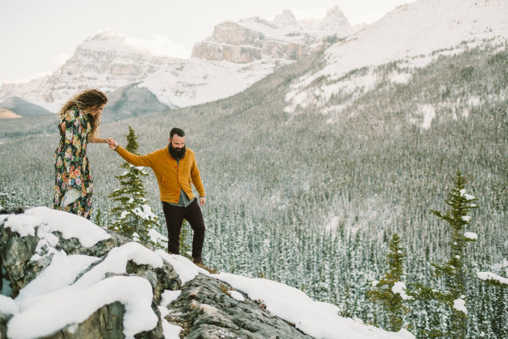 couple standing on mountain top with snow