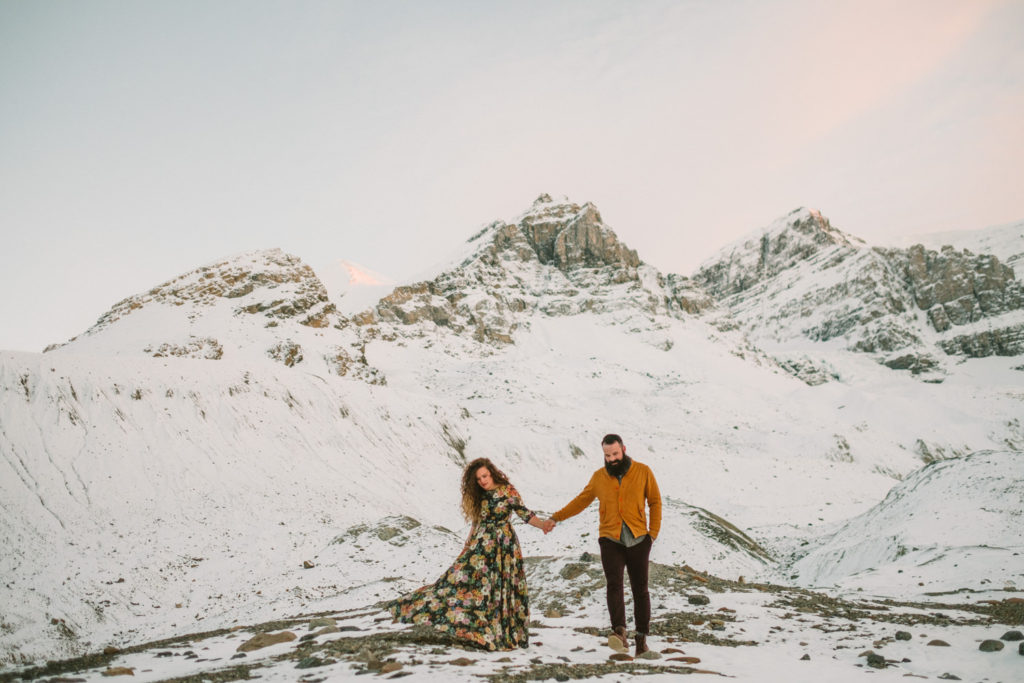 Couple at Columbia Icefields with snow on mountains