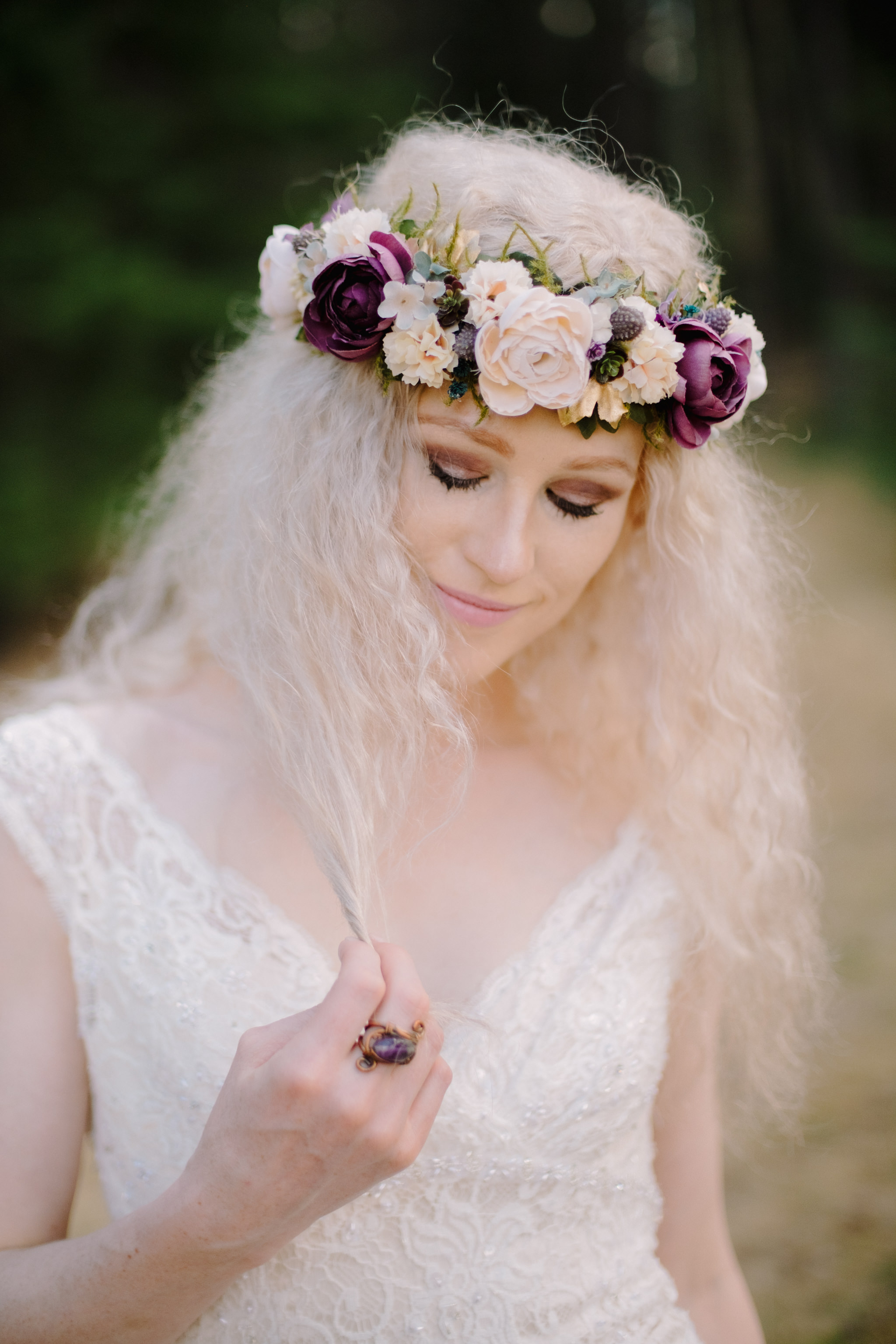 bride playing with hair while wearing flower crown