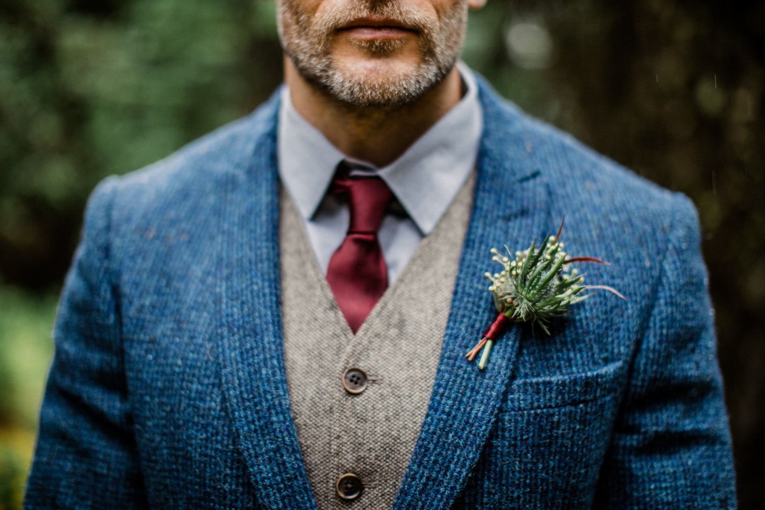 Groom wearing wool vest and suit in mountains